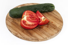 Raw cucumber and sliced tomato on the wooden board Stock Photo