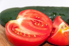 Raw cucumber and sliced tomato on the wooden board Stock Photography
