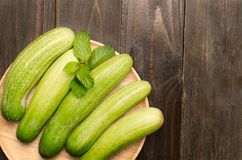 Raw cucumber. On wooden plate Royalty Free Stock Photography