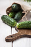 Raw cucumbers on cutting board. Selective focus Stock Images