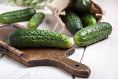 Raw cucumbers on cutting board. Selective focus Royalty Free Stock Photo