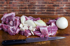 Raw cut meat, pork with cut onion and garlic on wooden cutting b. Oard. Red brick wall in background Stock Images