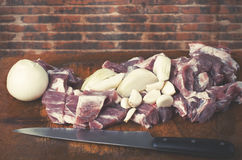 Raw cut meat, pork with cut onion and garlic on wooden cutting b. Oard. Red brick wall in background Royalty Free Stock Photos