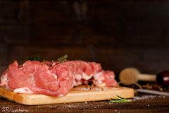 Raw meat slices on the board. Raw cut meat on a wooden board. Pork chunks for chops with pepper, salt, garlic and thyme Royalty Free Stock Images