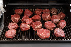 Raw cut medallions of veal on grill. A lot of raw cut medallions of veal on the grill. Outdoor barbecue Royalty Free Stock Images