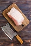 Raw cut of pork shoulder on board with knife or Kitchen ax. cleaver with fresh raw meat on black wooden background.  Stock Photography
