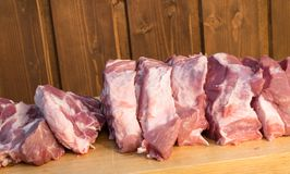 Raw cuting pieces of pork on wooden background. Piece of fresh boneless pork, neck part or collar. Big piece of red raw meat on a. Raw fat cuting pieces of pork Stock Image