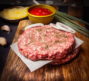 Raw cutlet for burger on cutting board with sauce, onions on wooden rustic background close up Royalty Free Stock Images