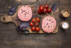 Raw cutlet for burgers, with cherry tomatoes and herbs on a cutting board, boarder, space  text on wooden rustic background top. Raw cutlet for burgers, with Royalty Free Stock Image