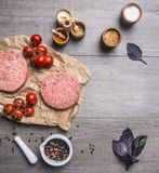 Raw cutlet for burgers, with cherry tomatoes and herbs on a packaging paper with unground pepper, knife for meat on wooden r. Raw cutlet for burgers, with cherry Stock Photo