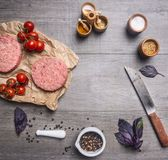 Raw cutlet for burgers, with cherry tomatoes and herbs on a packaging paper with unground black pepper, knife  meat on wooden r. Raw cutlet for burgers, with Stock Images