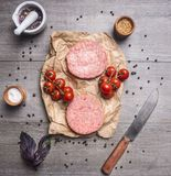 Raw cutlet for burgers, with cherry tomatoes and herbs on a packaging paper with unground black pepper, knife meat on wooden r. Raw cutlet for burgers, with Royalty Free Stock Photo