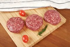 Raw cutlet of minced meat on a wooden cutting board. Raw cutlet of minced meat on a wooden cutting board Stock Photo