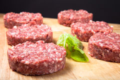 Raw cutlet of minced meat on a wooden cutting board Royalty Free Stock Photo