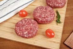 Raw cutlet of minced meat on a wooden cutting board. Raw cutlet of minced meat on a wooden cutting board Stock Images