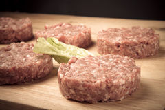 Raw cutlet of minced meat on a wooden cutting board. Toned Royalty Free Stock Image
