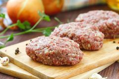 Raw cutlets on a chopping board and ingredients. Ready for cook Stock Images