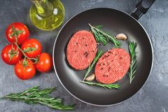 Raw cutlets pan with rosemary and garlic. Grey marble background. Stock Photo