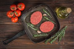 Raw cutlets pan with rosemary and garlic. Wooden brown backgroun Stock Photography