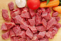 Raw cutting beef with vegetables on wooden plate Stock Images