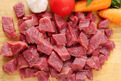 Raw cutting beef with vegetables on wooden plate Stock Photos