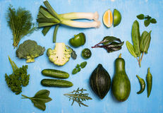 Raw detox green vegetable and herbs food set on blue wood backgr Royalty Free Stock Photography