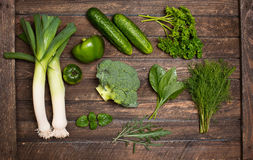 Raw detox green vegetable and herbs food set on wood table Royalty Free Stock Images