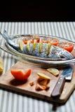 Raw dorada ready for roasting. Raw dorada with lemon and tomatos Royalty Free Stock Image
