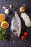 Raw dorado fish with ingredients. vertical top view. Raw dorado fish with ingredients on a table. vertical top view Stock Photography