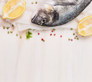 Raw Dorado fish with lemon and spices on white paper, wooden background, top view Stock Images