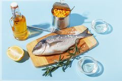 Raw dorado fish on a wooden board, ingredients for cooking and spices on a blue background royalty free stock image