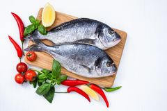 Raw dorado fish on wooden cutting board with vegetables on white table. stock photos