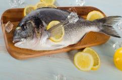 Raw dorado with lemon on  a wooden cutting board.  Royalty Free Stock Photos