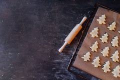 Raw dough cookies in Christmas tree shape ready to bake. Christmas Gingerbread cookies with baking paper on the tray on the dark background with wooden rolling royalty free stock image