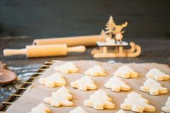 Raw dough cookies in Christmas tree shape ready to bake. Christmas Gingerbread cookies with baking paper on the tray on the dark background with wooden rolling stock images