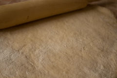 Raw dough flour rolling pin. On the table Royalty Free Stock Photography