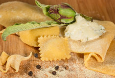 Raw dough and italian homemade ravioli with gorgonzola cheese, fresh artichoke and a few grains of black pepper., Royalty Free Stock Photography