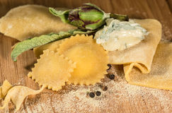 Raw dough and italian homemade ravioli with gorgonzola cheese, fresh artichoke and a few grains of black pepper. Royalty Free Stock Photo