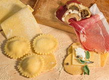 Raw dough and Italian homemade ravioli,open and closed,filled with mushrooms,prosciutto,ricotta cheese and aromatic herbs. Royalty Free Stock Image