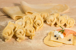 Raw dough and Italian homemade tortellini,open and closed,filled with ricotta cheese and smoked salmon. Stock Photo