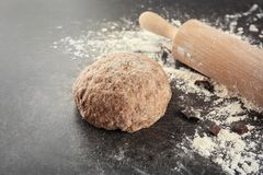 Raw dough with rolling pin. On table Stock Photography