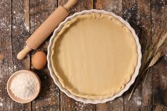 Raw dough and rolling pin. On wood Stock Image