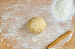 Raw dough with rolling pin and scattered flour on the wooden kitchen table. Baking background. Top view Stock Photo