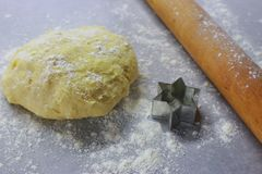 Raw dough with wooden rolling pin and star form for baking on table with flour. Cooking and baking background. Kitchen table with homemade dough. Baking Royalty Free Stock Photos
