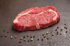 Raw dry aged beef steak with peppercorns. On a metal plate Stock Images