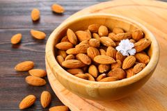 Raw dry nuts of almonds in a wooden bowl on a wooden table. Raw dry nuts of almonds in a wooden bowl on a wooden table Royalty Free Stock Photos