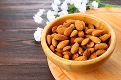 Raw dry nuts of almonds in a wooden bowl on a wooden table. Raw dry nuts of almonds in a wooden bowl on a wooden table Royalty Free Stock Photography