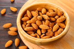 Raw dry nuts of almonds in a wooden bowl on a wooden table. Raw dry nuts of almonds in a wooden bowl on a wooden table Stock Images