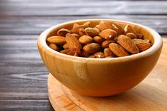 Raw dry nuts of almonds in a wooden bowl on a wooden table. Raw dry nuts of almonds in a wooden bowl on a wooden table Stock Photos