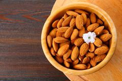 Raw dry nuts of almonds in a wooden bowl on a wooden table. Raw dry nuts of almonds in a wooden bowl on a wooden table Royalty Free Stock Photo